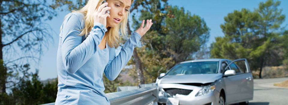 lady on phone with wrecked car